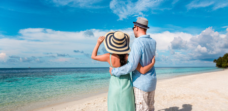 newlywed couple: Couple on vacation walking on a tropical beach Maldives. Man and woman romantic walk on the beach. Stock Photo
