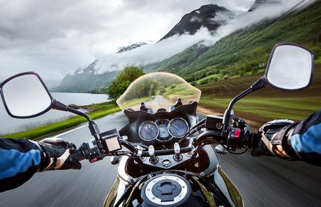 Motorista monta una motocicleta en la lluvia. Vista en primera persona. Foto de archivo