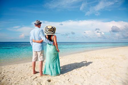 femme romantique: Couple en vacances marche sur une plage tropicale aux Maldives. Homme et femme promenade romantique sur la plage. Banque d'images
