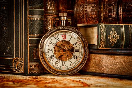 Antiguo reloj de bolsillo de la vendimia en el fondo de libros antiguos
