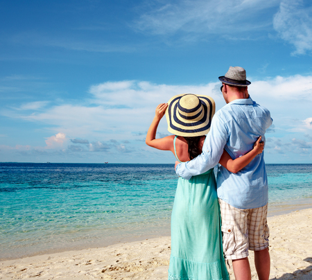 strolling: Couple on vacation walking on a tropical beach Maldives. Man and woman romantic walk on the beach. Stock Photo