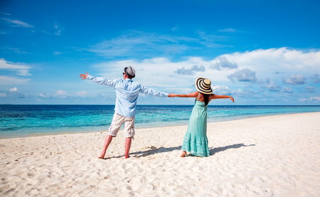 back to back couple: Couple on vacation walking on a tropical beach Maldives. Man and woman romantic walk on the beach. Stock Photo