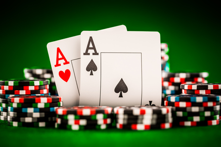aces: Stack of chips and two aces on the table on the green baize - poker game concept