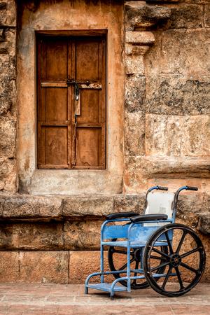 paraplegico: silla de ruedas sobre un fondo de un muro de piedra