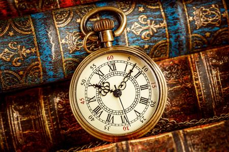 오래 된 책의 배경에 빈티지 골동품 포켓 시계