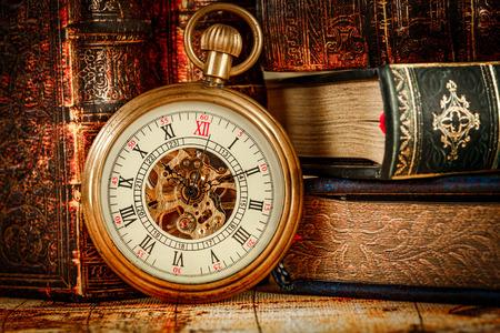 antique background: Vintage Antique pocket watch on the background of old books
