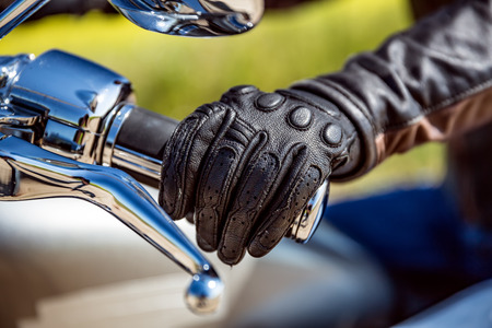 throttle: Human hand in a Motorcycle Racing Gloves holds a motorcycle throttle control. Hand protection from falls and accidents.