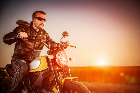 postproduction: Biker man wearing a leather jacket and sunglasses sitting on his motorcycle looking at the sunset, racing on the road. Filter applied in post-production.