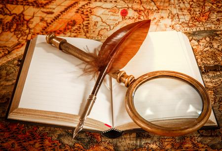 libros antiguos: Todavía de la vendimia vida - lupa, libro antiguo y pluma pluma de ganso tumbado en un viejo mapa en 1565.