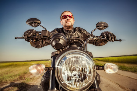 postproduction: Biker in a leather jacket riding a motorcycle on the road. Filter applied in post-production.