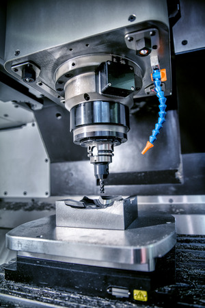 Metalmecánica fresadora CNC. Cortar metal moderno tecnología de procesamiento. Pequeña profundidad de campo. Advertencia - tiroteo auténtico en condiciones difíciles. Un poco de grano poco y tal vez borrosa. Foto de archivo - 57580656