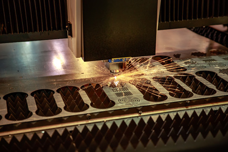 lasercutting: CNC Laser cutting of metal, modern industrial technology. Small depth of field. Warning - authentic shooting in challenging conditions. A little bit grain and maybe blurred.