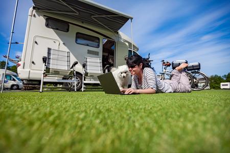 Mujer en la hierba con un perro mirando un ordenador portátil. Alquiler de coches de camping. viajes de vacaciones de la familia, viaje de vacaciones en autocaravana