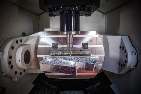 Metaalbewerking CNC freesmachine. Snijden metaal moderne verwerkingstechnologie. Kleine scherptediepte. Waarschuwing - authentieke opname in moeilijke omstandigheden. Een beetje graan en misschien wazig.