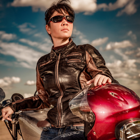 motor bike: Biker girl in a leather jacket and sunglasses sitting on motorcycle
