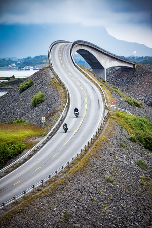 Two bikers on motorcycles. Atlantic Ocean Road or the Atlantic Road (Atlanterhavsveien) been awarded the title as Norwegian Construction of the Century.