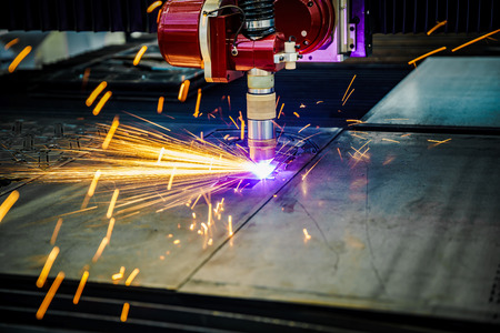 lasercutting: CNC Laser plasma cutting of metal, modern industrial technology. . Small depth of field. Warning - authentic shooting in challenging conditions. A little bit grain and maybe blurred. Stock Photo