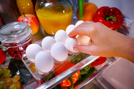 refrigerator: Chicken eggs on a shelf open refrigerator Stock Photo