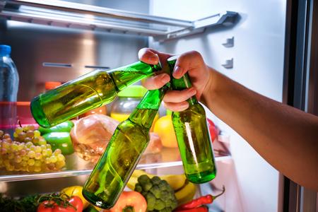 Man taking beer from a fridge Standard-Bild