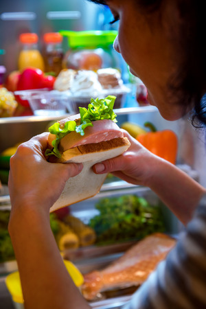 woman eat: Hungry Woman holding a sandwich in his hands and standing next to the open fridge. Unhealthy food.