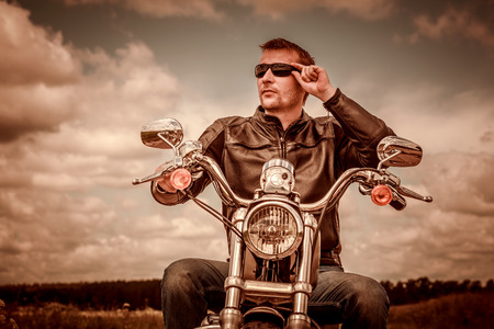postproduction: Biker man wearing a leather jacket and sunglasses sitting on his motorcycle. Filter applied in post-production. Stock Photo