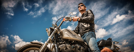 hombre: Motorista hombre que llevaba una chaqueta de cuero y gafas de sol sentado en su motocicleta.