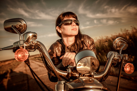 applied: Biker girl with sunglasses sitting on motorcycle. Filter applied in post-production.