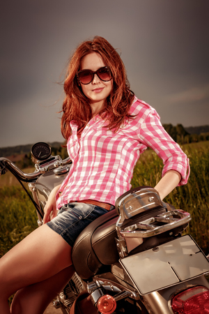 postproduction: Biker girl with sunglasses sitting on motorcycle. Filter applied in post-production.