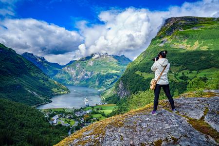 Geiranger fjord, Beautiful Nature Norway panorama. Nature photographer tourist with camera shoots.