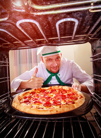 grates: Chef prepares pizza in the oven, view from the inside of the oven. Cooking in the oven.