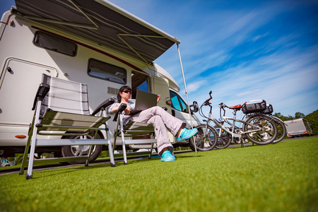 voyage: Woman sitting on a chair near the camper and looking at a laptop. Caravan car Vacation. Family vacation travel, holiday trip in motorhome Stock Photo