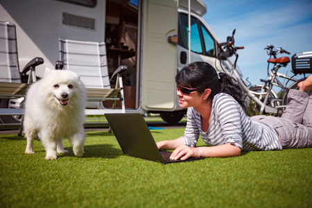recreational vehicle: Woman on the grass with a dog looking at a laptop. Caravan car Vacation. Family vacation travel, holiday trip in motorhome