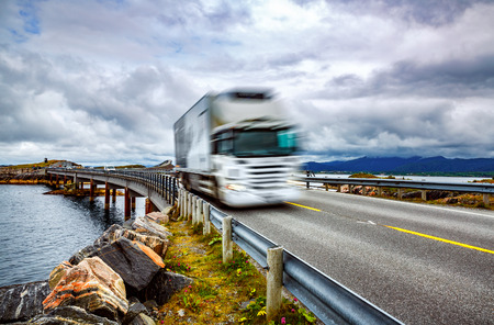 diagonal: Truck and highway at sunset. Truck Car in motion blur. Atlantic Ocean Road or the Atlantic Road (Atlanterhavsveien) been awarded the title as Norwegian Construction of the Century. Stock Photo