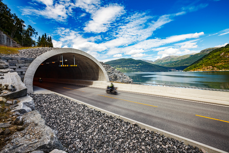 Mountain road in Norway. The entrance to the tunnel. Biker racing on the track in the tunnel