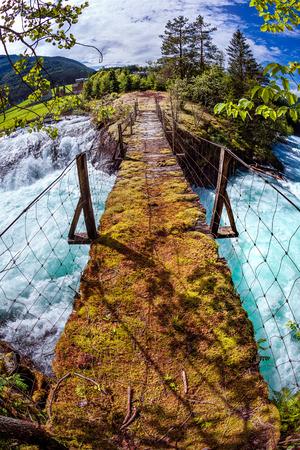 bridge in nature: Suspension bridge over the mountain river. Beautiful Nature Norway natural landscape. Fisheye lens Stock Photo