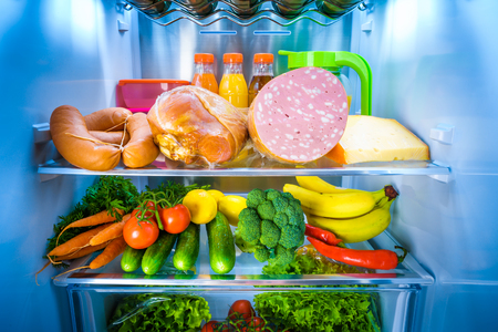 cold storage: Open refrigerator filled with food.
