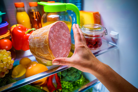 Human hands reaching for food at night in the open refrigerator Stock Photo