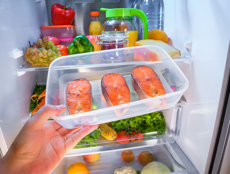 Raw Salmon steak in the open refrigerator Stock Photo