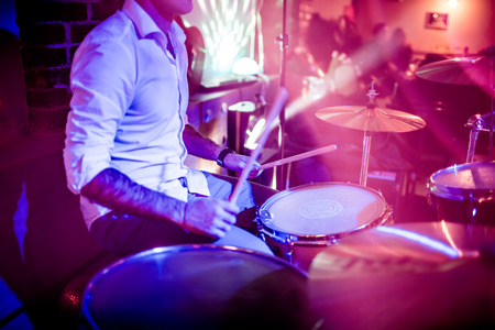 Drummer playing on drum set on stage. Warning - Focus on the drum, authentic shooting with high iso in challenging lighting conditions. A little bit grain and blurred motion effects. Stock Photo - 70361015