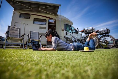 Mujer en la hierba, mirando la computadora portátil cerca del? Amping. Caravana de vacaciones. Viaje de vacaciones en familia, viaje de vacaciones en autocaravana