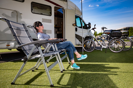 campsite: Woman resting on a сamping chair on the nature. Caravan car Vacation. Family vacation travel, holiday trip in motorhome Stock Photo