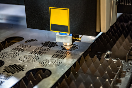 lasercutting: CNC Laser cutting of metal, modern industrial technology. . Small depth of field. Warning - authentic shooting in challenging conditions. A little bit grain and maybe blurred. Stock Photo
