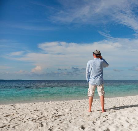 Beach vacation. Man and tropical beach in the Maldives. photo