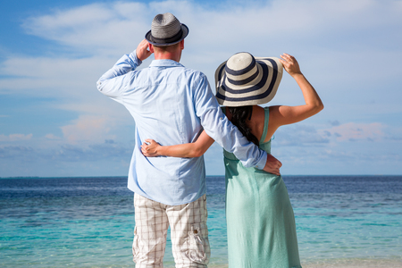 Couple on vacation walking on a tropical beach Maldives. Man and woman romantic walk on the beach. photo