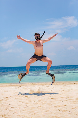 Funny man jumping in flippers and mask. Holiday vacation on a tropical beach at Maldives Islands. photo