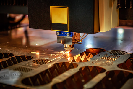 CNC Laser cutting of metal, modern industrial technology. . Small depth of field. Warning - authentic shooting in challenging conditions. A little bit grain and maybe blurred. Stock Photo