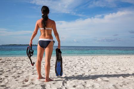 Girl in bikini with snorkeling gear on the beach Maldives. Stock Photo