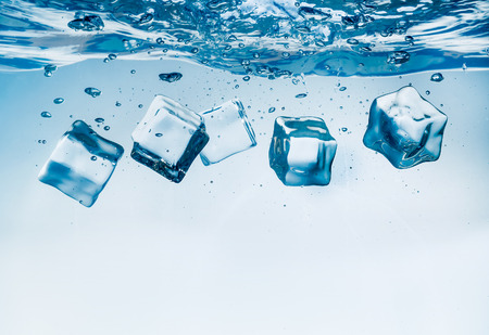 sinking: Ice cubes falling into the water sinking to the bottom. Abstract background.