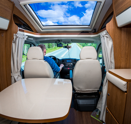 Man driving on a road in the Camper Van. Caravan car Vacation. Family vacation travel, holiday trip in motorhome photo