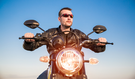 Biker man wearing a leather jacket and sunglasses sitting on his motorcycle looking at the sunset. photo